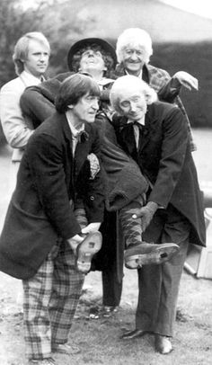 """Peter Davison (Five), Jon Pertwee (Three), Patrick Troughton (Two) and Richard Hurndall (One, in place of William Hartnell, who died in 1975) carry a Tom Baker (Four) wax figure during a photoshoot for """"The Five Doctors"""""""