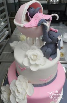 Celebrate a new baby girl's arrival with this elephant themed pink and white cake.