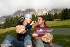 Foto de stock : Italy, Alto Adige, young couple sitting in valley eating bread