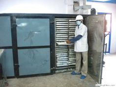 The man inserting trays into the Tray Dryer to get the best powder drying from the machine.