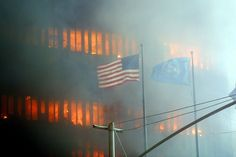 An American flag flies in the foreground as one of the World Trade Center towers burns in the background 11 September 2001 in New York. Two hijacked airplanes crashed into the two landmark skyscrapers. We Will Never Forget, Lest We Forget, Barack Obama, World Trade Center Collapse, Photo Choc, Day Of Infamy, Broken Window, 11. September, Sad Day