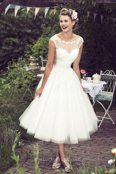 This rustic wedding dress is perfect for a relaxed country wedding. A-line wedding dress features illusion neckline cap sleeves lace bodice topped by tea length tulle skirt.
