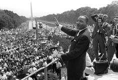 King waves from the steps of the Lincoln Memorial on Aug. 28, 1963, as the throng assembled for the March on Washington stretches into the distance toward the Washington Monument.