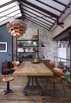industrial dining room with thick wood top of this dining table is supported by a cast iron factory table base modern dining