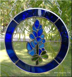 """Approximately 7"""" Diameter Texas Blue Bonnet.  33 piece, zinc framed with chain.    Approximately 7"""" Diameter Texas Blue Bonnet, constructed in Tiffany Style. The flowers are a Wispy Cobalt with Streaky Green leaves. The background glass is clear Antique style glass and the border is a Cobalt Blue water glass."""