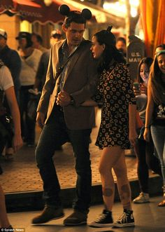 Disney darlings: John Mayer holds hands with his girlfriend of one year, Katy Perry, as they roam Disneyland at night on Sunday