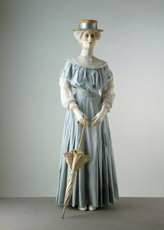 ~A circa 1905 summer day dress of pin-striped cotton. The blue and white color combo was especially popular for seaside and boating related fashion.  Like most turn-of-the-century summer outfits, the ensemble is topped off with a boater hat~