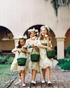 Three flower girls in Geminola dresses sprinkling rose petals down the aisle