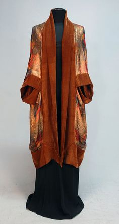 LIBERTY, PARIS, PRINTED LAME and VELVET COCOON, c. 1920. Gold lame printed with horizontal bands of flowers in red, yellow and blue trimmed in wide bands of brown silk velvet having subtle gold stripe, matching velvet lining, labeled. L-43.