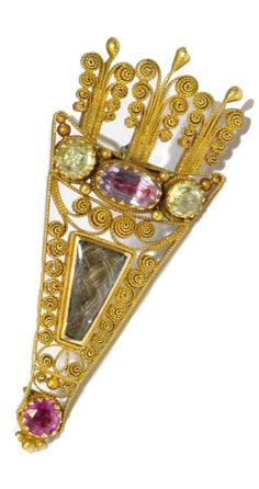 A Georgian quiver brooch, English, circa 1820. Brooch in the form of a quiver of arrows, set with pink topaz, ruby and chrysolite, with a central compartment filled with plaited hair, and intricate cannetille gold work throughout. Engraved 'Amitie' to the reverse. #Georgian #antique #brooch