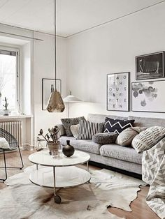 grey and neutral living room with gold pendant lamp, round two layered coffee table and grey couch