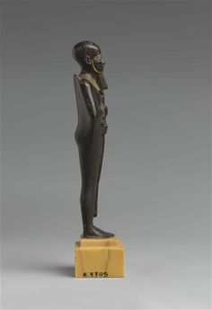 Bronze electrum incrusted statuette of deity Ptah, with a well-rounded back...25th dynasty. Egypt. Louvre museum, Paris.