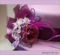 Sugar flower, ribbon and feather arrangement for a hat-shaped cake by Cakes by No More Tiers.