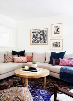 Living room in a California eclectic home, with vintage indigo and batik patterned throw pillows, beige sectional sofa, black and white print gallery wall, solid wood tripod coffee table and oversized vintage Persian area rug in pink and navy blue.