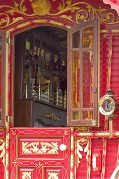 Gold-emellished/Illuminated Red arched door with opening panelled window.