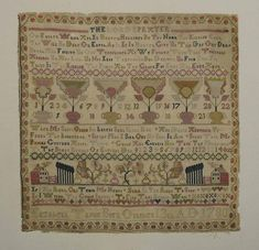 Sampler, 1780 to 1795.  BIG BOLD BEAUTIFUL FLOWERS are just as a little girl would make them.  They're fanciful and boldly colored.  They make this otherwise standard sampler something remarkable.