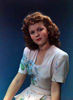 Beautiful Shirley Temple ca. 1943, wearing a peplum dress with a lovely floral motif.