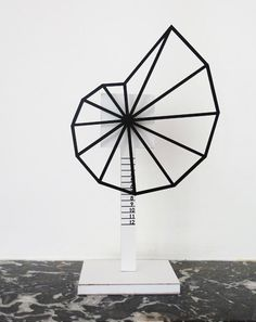 A prototype clock that tells the time in a straight line by replacing the hands with a pivoting shell-like structure.