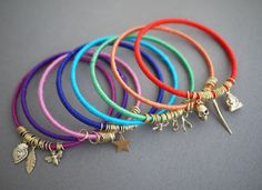 DIY Wrap Bangles. Take a pre-existing bangle and glue the ends of embroidery thread. The thread is wrapped around the bracelet. Add charms and extra jump rings after.