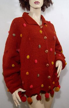 Hello! I love sweaters and I love the unusual....this sweater is a rich, warm rust or brick colour, and it fastens with cool wooden buttons. There are 2 deep, horizontally set pockets near the bottom. I love the pompoms, of course! Its in excellent condition aside from 2 missing pompoms on the left hand side. Typical drop shoulder seam design of the 1980s. To clean this sweater, home or professionally dryclean, because of the pompoms. Labelled World Folk Art, Nanaimo, Canada. Another…