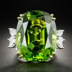 A gem and a knockout! No two-dimensional image can begin to do justice to this absolutely amazing, impressively proportioned (56 carats !- over 1-inch long!), luscious, rich forest green/lime green, gem Peridot. This mid-20th century marvel glistens and glows between sizzling sprays of sizable (3.00 carats total weight), bright-white and sparkling marquise diamonds set in platinum. The peridot setting and ring shank are rendered in rich 18K yellow gold. Extraordinary in every way (even the…