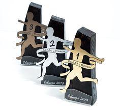 Statuetki na zawody sportowe wykonane z trzech materiałów: drewna, laminatu grawerskiego i przezroczystej pleksi.