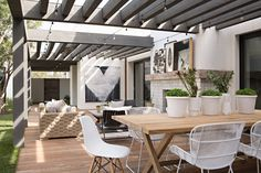 Contemporary backyard patio. Grey pergola. Outdoor dining. By Eric Olsen Design