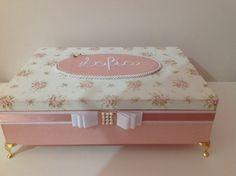 Caixa em mdf, inteira forrada com tecido, bordada os 2 lados da tampa, com pezinhos de metal que pode ser na cor dourada ou prata.  Medidas 34x24x8,5 (cm) + Pezinhos    Tecido da base, poa rosa , e na tampa florzinhas delicadas.