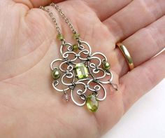 A lovely celtic cross necklace, handcrafted with wire wrapped sterling silver, and peridot gemstones. Handmade peridot necklace by
