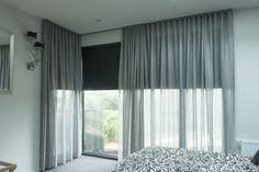 Black roller blinds behind sheer voiles