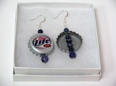 Now, I dont want to point any fingers but...if youre an avid drinker of the beer whose recycled bottle caps are pictured above and female, you may just be a Redneck Woman and darn proud of it too! Show that pride, sarcasm, wit, keen kitschy fashion sense...whatever it may be with these BrigaBauble original dangling earrings handmade from a pair of recycled beer bottle caps from a leading-brand beer accented by 6mm and 10mm semi-precious, swirling blue and white round Lapis Lazuli beads… Green Earrings, Women's Earrings, Redneck Costume, Redneck Woman, Beer Bottle Caps, Lapis Lazuli, Costumes For Women, Earrings Handmade, Costume Ideas