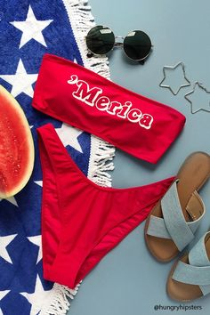 """A knit bandeau bikini top featuring a front """"Merica"""" graphic, a straight cut, an elasticized trim, removable cups, and a back hook closure. Matching bikini bottoms available."""