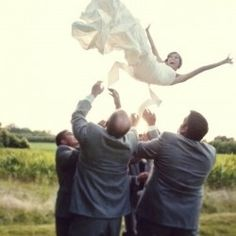 Groomsmen throwing bride in the air