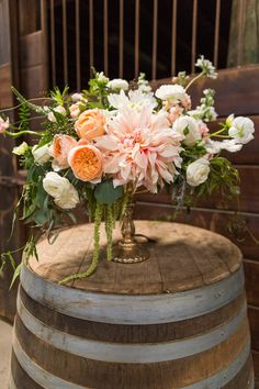 welcome your guests with beautiful flowers of cafe au lait dahlias, juliet roses and ranunculus on a wine barrel