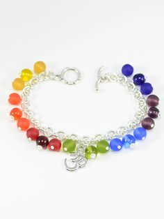 Bracelet 1259 - A day or evening Chakra charm bracelet featuring a traditional Ohm charm beaded with glass beads corresponding to the main seven Chakras. A fashionable way to balance your energy.
