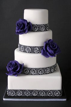 Deep purple roses and a black and silver floral pattern glam up this modern white cake.