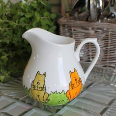 Let these charming cats add a homely touch to teatime with this very special milk jug. Hand painted fine bone china, this mug features Laura's feline friends, brown puss, Jess the silver tabby and old ginger Tom.Sat among the long green grass they are soaking up some sunshine and getting lost in their cat-like thoughts.Laura's Colourful Cats design was inspired by her own cat sitting in her front garden. It seemed like all of the neighbours cats had come to visit to have a chat with…