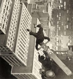 Man balancing on a piece of wood on the roof of a skyscraper, 1939
