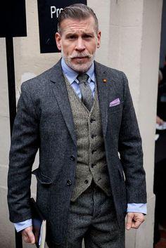 La laine reste le propre de l'élégance et la matière par excellence du costume. On trouve dans ce look un ensemble de laine déclinée en couleurs et vêtements différents. Le pantalon gris est surmonté d'un gilet beige et d'une veste à reflets bleu. Le mannequin va jusqu'à ajouter une cravate de laine afin de pousser le détail. A noter la moustache et la coupe de cheveux travaillée.