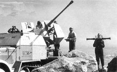 A SdKfz 7/2 halftrack with a armored cab along with a mounted 37mm Flak 36 gun used for anti aircraft duties. Note the soldier on the right using a range finder.