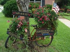 "Old bicycle, baskets of red flowers, flags, ""Happy 4th of July"" and ""Independence Day Gatherings"" signs ... love it!"