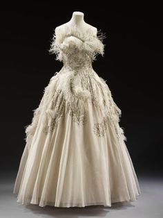 """""""Evening dress, 1950-1955 This evening gown was designed by Pierre Balmain (1914-82), and may have been a debutante's presentation dress. The gown is embellished with ostrich feathers, sequins and rhinestones. Working such a light-weight fabric required great skill, and would have been commissioned from a specialist workshop such as Lesage."""" (quote) via elisa-rolle.livejournal.com"""