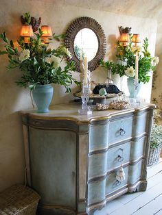 I like the faded looking painted chest, not crazy about the mirror, & the arrangement on the chest just doesn't work. The flowers are engulfing the sconces, and the handbag in a bowl as a decoration seems contrived.