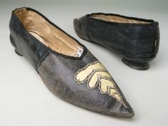 Manchester City Galleries Item 1953.69  1790-1810 Black kid over white linen, with yellow kid insertion. Bound with black silk ribbon.    Leather soles. Sharply pointed toe and rounded fronts. Insertion of yellow kid over front, edged with white silk worked in chain stitch, forming roughly triangular shape over toe.