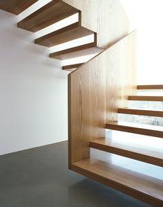Kragarmtreppe mit handlaufhohen Brüstungswangen. Die Treppe scheint im Bereich des unteren Laufs zu schweben