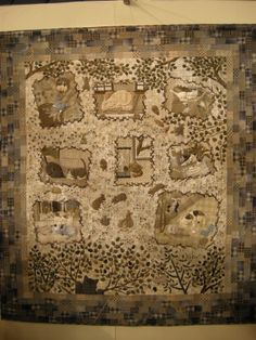 This is a very Japanese quilt; taupe, a mix of pieced and appliquéd work, pictorial, featuring animals, and it's cute and charming. It depicts a group of mice making a map and marking out in which houses there is a cat in residence. The mice are talking about all the mischief a cat is up to. The neighbourhood feline boss sits in the tree and looks down at the mouse conference.