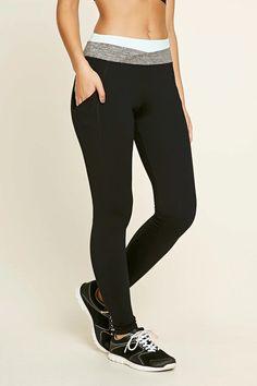 A pair of knit leggings featuring a heathered trim, mesh side pockets, a hidden key pocket, an elasticized contrast waist, and moisture management.