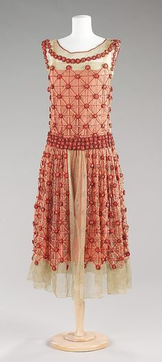 "Designer: Jeanne Lanvin (French, 1867-1946)  ""Roseraie"" silk dress, ca.1923  The ribbon flower head designs of ""Roseraie"" are reminiscent of the floral designs of Art Nouveau architect Charles Rennie Mackintosh and his wife Margaret MacDonald Mackintosh . Lanvin's version was originally created as a swatch at one of her embroidery studios in 1918-1919, according to Dean L. Merceron in his book ""Lanvin."" It was later used in this latticework to suggest a sense of youthful beauty."