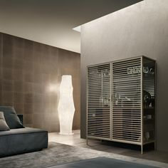 #Rimadesio Bar cabinet Alambra with structure in palladio aluminum, doors, side panels and shelf in transparent gray glass, gray mirror glass back panel, top in mat lacquered glass palladio. Fridge cabinet with open unit and door in walnut, top and handle in castoro regenerated leather.