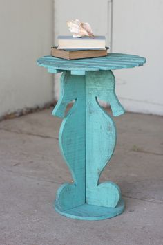 """This light-hearted wooden table is painted in bright teal and features a clever seahorse design with a slatted wood top. Easily collapsible, this table is portable and perfect for poolside fun. 17""""d x 25""""tsimple assembly required"""